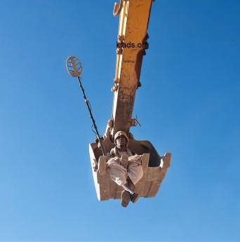 Старателя подняли с прибором, чтобы он смог проверить отвесную скалу прибором на наличие золота